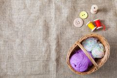Colored threads and wooden buttons and a wicker basket are on sackcloth in the corner of the frame. Balls of colored threads and wooden buttons and a wicker stock photo