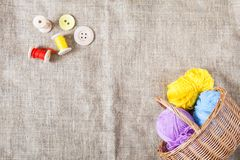Colored threads and wooden buttons and a wicker basket are on sackcloth in the corner of the frame. Balls of colored threads and wooden buttons and a wicker royalty free stock images
