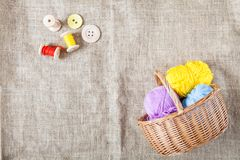 Colored threads and wooden buttons and a wicker basket are on sackcloth in the corner of the frame. Balls of colored threads and wooden buttons and a wicker stock photos