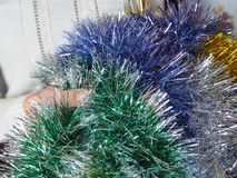 Colored tinsel in woman hands. Royalty Free Stock Photos