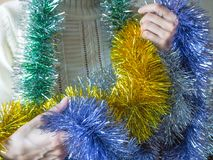 Colored tinsel in woman hands. Stock Images