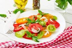 Colored tomato salad with onion and basil pesto. Vegan food stock photos