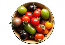 Colored tomatoes in bowl isolated Royalty Free Stock Images