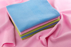 Colored towels folded stack. Neatly folded towels lay on a crumpled towel Royalty Free Stock Photography