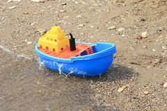 Colored toy boat. Kids beach colored toy boat Royalty Free Stock Photos