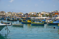 Colored traditional fishing boats Luzzu in Marsaxlokk harbor,. MARSAXLOKK, MALTA - AUGUST 2, 2015: Colored traditional Maltese boats Luzzu moored in the of Stock Photos