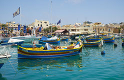 Colored traditional fishing boats Luzzu in Marsaxlokk harbor,. MARSAXLOKK, MALTA - AUGUST 2, 2015: Colored traditional Maltese boats Luzzu moored in the of Royalty Free Stock Photos