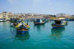 Colored traditional fishing boats Luzzu in Marsaxlokk harbor,. MARSAXLOKK, MALTA - AUGUST 2, 2015: Colored traditional Maltese boats Luzzu moored in the of Royalty Free Stock Photography