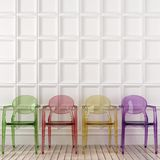 Colored transparent chairs and white wall Royalty Free Stock Photography
