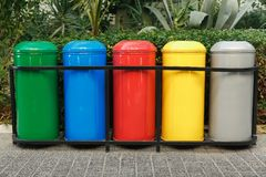 Colored trash containers for garbage separation. Taking care of nature and ecology. The greenery around. Containers for plastic, paper, glass and metal Stock Image