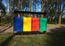Colored trash containers in a park Stock Images