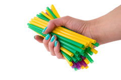 Colored tubules for a cocktail in a female hand. Bunch of colored tubules for a cocktail in a female hand Royalty Free Stock Image