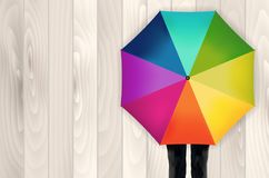 Colored umbrella, legs and wooden background Stock Photos