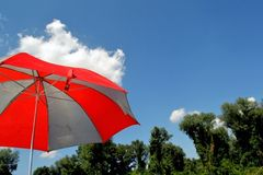 Colored umbrella over white clouds. Summer beautiful, tranquil blue sky full of fluffy clouds stock photo