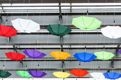Colored umbrellas hanged by wires Stock Photo