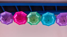 Colored umbrellas hanging from the ceiling stock photos