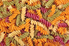 Colored uncooked italian pasta fusilli as background Stock Images