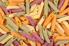Colored uncooked italian pasta penne as background Royalty Free Stock Images