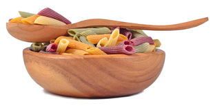 Colored uncooked italian pasta penne in a wooden bowl on a white Royalty Free Stock Image