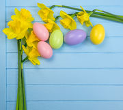 Colored vernal flowers and eggs. Colored vernal flowers on blue wooden background to Easter greeting card with pastel eggs stock photo