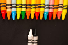Colored versus black and white crayons Royalty Free Stock Photos