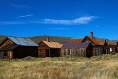 Colored vintage old looking photo of empty streets of abandoned ghost town Bodie in California, USA royalty free stock photos