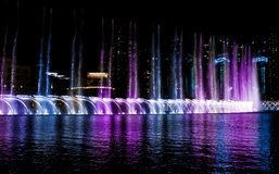 Colored water fountain at night stock image