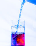 Colored Water in a Glass. A pitcher of blue liquid being mixed in a glass of red liquid Stock Photos