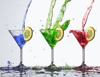 Colored water splash in glass. In white background Royalty Free Stock Photo