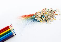 Colored watercolor pencils of rainbow colors and shavings from them after sharpening on a white background.