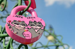 Colored wedding locks. Moscow, Russia - June 25, 2015: Pink wedding lock with the image of two animals at the blue sky background on Luzhkov bridge in Moscow royalty free stock photography