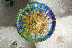 Colored wheel mosaic of colored ceramic tile by Antoni Gaudi at his Parc Guell, Barcelona, Spain stock photo