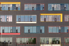 Colored windows of the building with the sky reflected in the glass. Geometric background. Building`s facade Royalty Free Stock Image