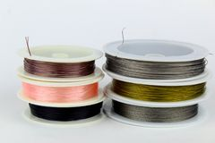 Colored wire for making jewelry from natural stones and natural materials. Wire on white plastic coils stock photos