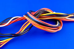 Colored wires. From PC power supply isolated on blue background Royalty Free Stock Photos