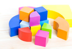 Colored wooden blocks, cubes, build on a light wooden background Stock Photos