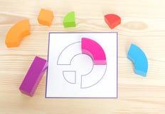 Colored wooden blocks lie near the template that needs to be repeated. Colored wooden blocks, cubes, build on a light wooden backg. Art; blocks; math; childhood Stock Photo