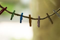 Colored wooden clothespins hanging on a wire. Close up stock photo