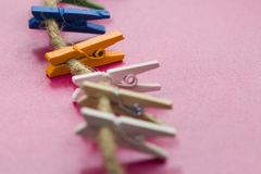 Colored wooden clothespins hanging on a wire. Close up stock images