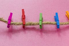 Colored wooden clothespins hanging on a wire stock images