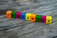 Colored wooden cubes with letters. the word companies is displayed, abstract illustration. Wooden cubes with letters. the word companies is displayed, abstract royalty free stock photo
