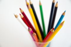 Colored wooden pencils for drawing in a glass stand on a white background. Children`s multi-colored pencils for drawing royalty free stock photography