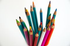 Colored wooden pencils for drawing in a glass stand on a white background. Children`s multi-colored pencils for drawing stock photos