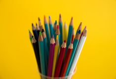 Colored wooden pencils for drawing in a glass stand on a white background. Children`s multi-colored pencils for drawing stock photo