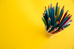 Colored wooden pencils for drawing in a glass stand on a white background. Children`s multi-colored pencils for drawing royalty free stock image