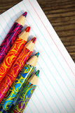 Colored wooden pencils. On a sheet of white paper Stock Images