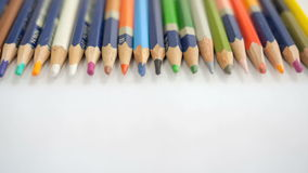 Colored wooden pencils on white paper stock footage