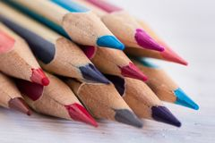 Colored wooden pencils on a white wooden table. Macro. Close up. Side view royalty free stock photography
