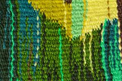 Colored wool knitted carpet texture. Knitting by hand, interlacing threads, abstract pattern, nationality, tradition royalty free stock photo