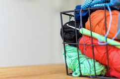 Colored Yarn in metal basket with crochet hook. Colored yarn in the right side of the image. Basket placed om table. Crochet hook in focus. Space left empty Royalty Free Stock Photo